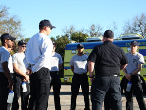 EMT Cadets standing outside the AMBUS, in a circle, receiving instruction