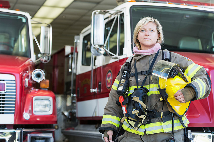 female firefighter in full gear, standing proud